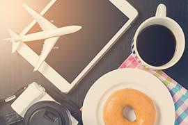 Flieger auf Tablet neben Kaffee