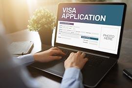 Mann beantragt Visum auf einem Laptop
