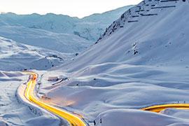 Beleuchtete Straße in verschneiten Bergen
